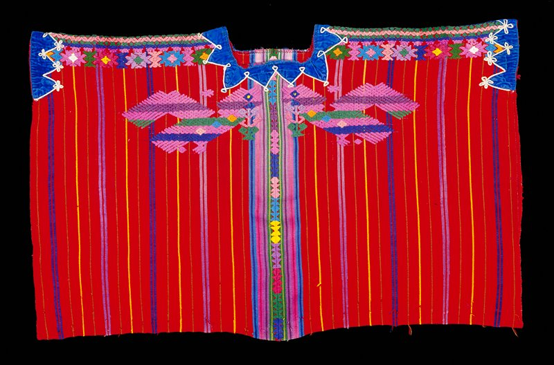 Two panel huipil with square cut neck opening; red ground cloth with thin stripes in brown, blue, yellow and purple; randa extends down entire center seam; open on sides; pair of brocaded birds, predominantly in purple, on front and back below collar with multicolored brocaded geometric patterns at shoulders and down center of chest and back; blue velvet at collar and shoulders.