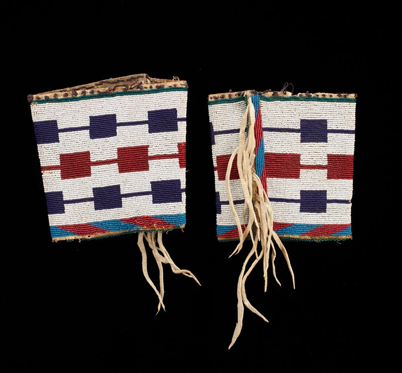 leather cuffs; band of red and blue beaded parallelograms at bottom and side of each, with delicate turquoise bead edging; body is white beaded field with three rows of rectangles connected with horizontal bars--two purple rows and one red row; green beads at top