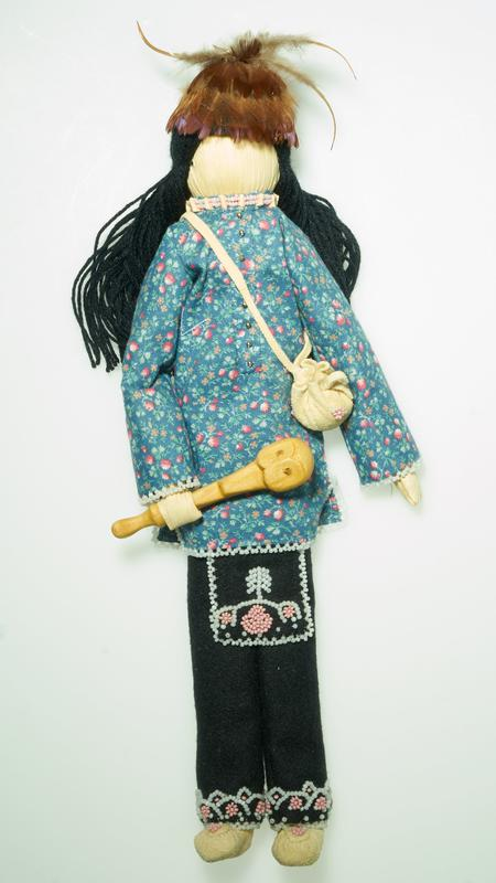 "standing faceless doll with long black yarn hair; doll wears a flowered shirt with blue ground and tiny orange and pink flowers, with white beading at hems and cuffs and silver bead ""buttons""; black wool pants with black wool apron; both apron and pants are decorated with pink, pale green and white beads in floral motifs; leather moccasins and pouch with shoulder strap decorated with pink and pale green beads in floral motifs; pink and white beaded choker necklace; doll holds a wooden club with a stylized owl face; separate dome-shaped hat with rush-colored feathers overall--3 long pointed feathers on top of hat"