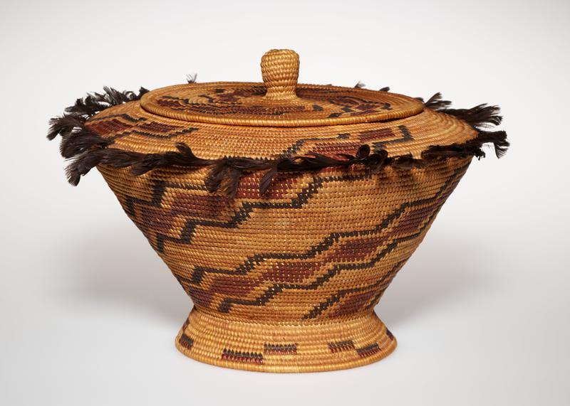 ring foot; outward-flaring sides of basket with flat shoulder and wide mouth; tight-fitting lid with ring beneath rim; basket and cover decorated with stepped bands of medium and dark brown on light brown ground; dark brown quail feathers around point of shoulder