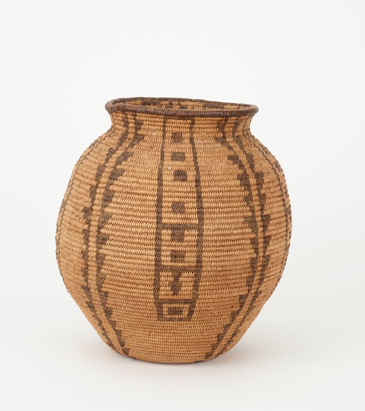 coiled basket in jar form with flat foot; slightly outward-flaring sides, tapering in to subtle shoulder; wide outward-flaring mouth rim on wide, very short neck; light brown with vertical dark brown designs of pairs vertically-placed triangles and ladder-like designs with rectangles and arrowheads