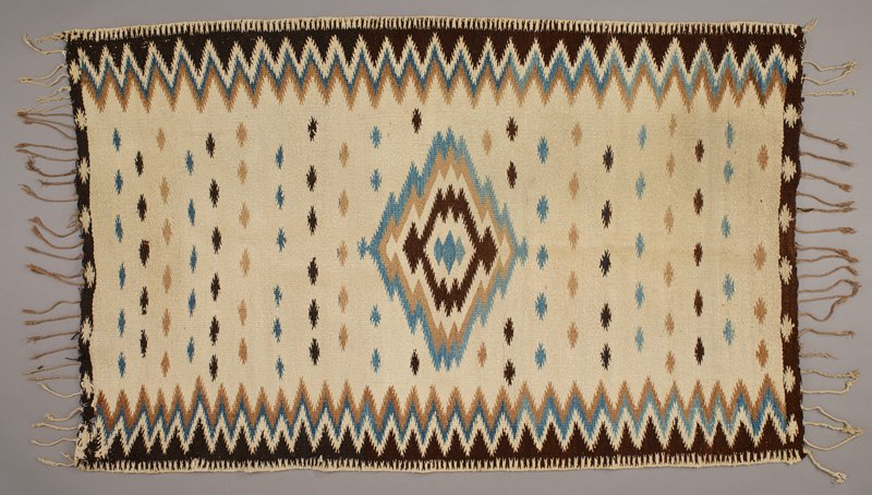 cream, dark brown, light brown and blue; cream ground; central radiating stepped diamond design with three blue diamonds at center; diamond shaped starbursts in rows of like colors; brown border with cream starbursts at short ends; stepped zigzags and brown triangle bands at long sides; twisted medium tan tassels/fringe at short ends