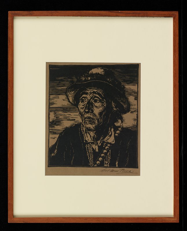 Native American with wrinkled face wearing hat and necklaces; tan paper