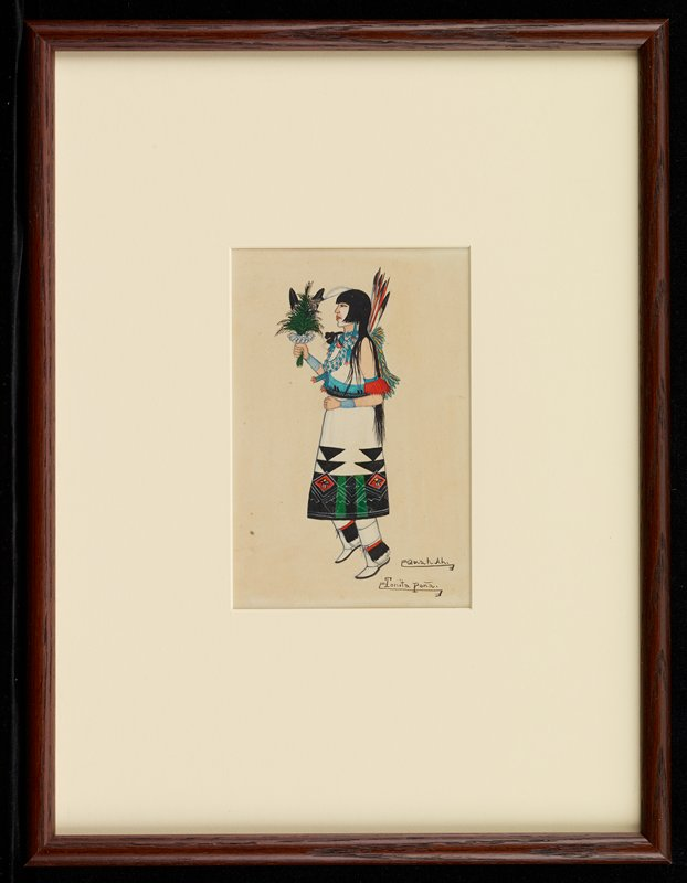 standing woman in profile from PL, wearing a white sleeveless dress with predominately black, green and red patterned band at bottom, with black triangles and red diamonds; woman wears white leggings and moccasins with black, red and white fringed elements around ankles; woman also wears blue beaded necklaces, with feathers on her upper back and holds a bouquet with white flowers, green foliage and feathers; woman has long black hair