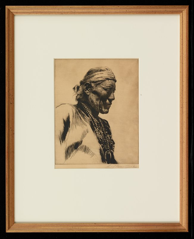 portrait of a Native American man wearing a headband and many beaded necklaces, looking toward PL