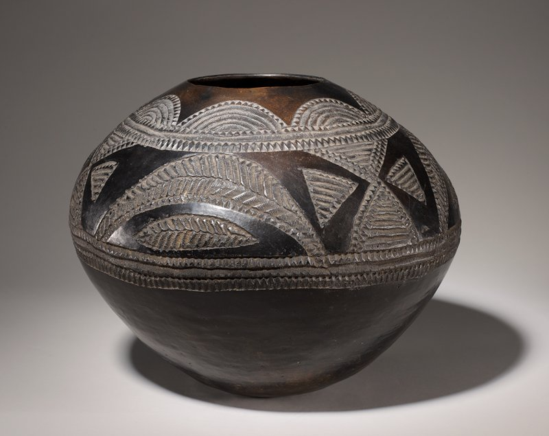 Large pot with flaring midsection and tapering shoulder; decorated with incised textured half-circles below mouth and band of leaf-like shapes alternating with 4 triangles between 3 textured bands