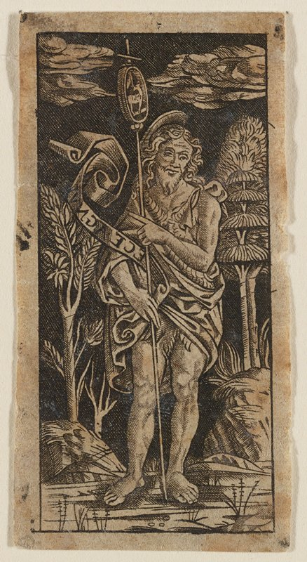 male figure wrapped in robes at center, holding staff with cross at top and image of lamb within oval; figure points an inscription with his PL hand on the unrolling, wind-blown scroll in his PR hand; stylized trees and boulders in background