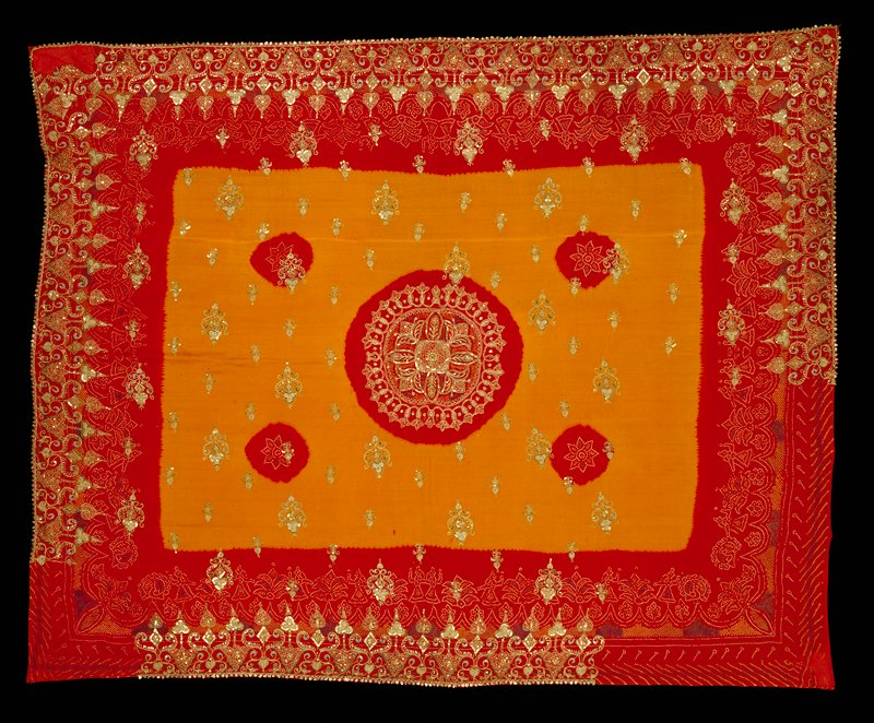 Red silk with large yellow tie-dyed field at center with 5 red areas; printed floral designs at border and inside red areas, made up of small rectangles; sequins and gold, aqua and green embroidery around bottom and portions of right, left and top edges, at center and through yellow field