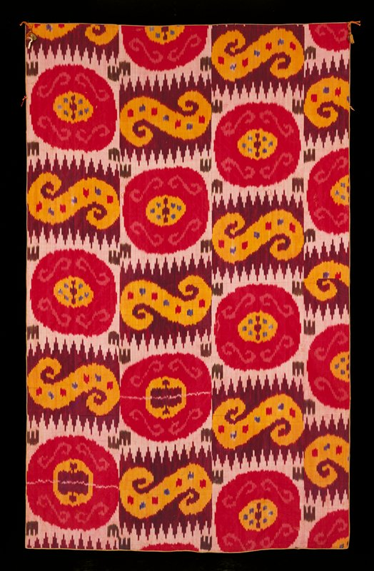 Strips of silk ikat warp, red silk weft, sewn together; repeating pattern of yellow circle with purple and blue patches inside of pink circle with 4 S-shaped swirls and purple patches with yellow S-shaped swirls and red and blue patches; backed with floral print in pinks and white; tassels at corners