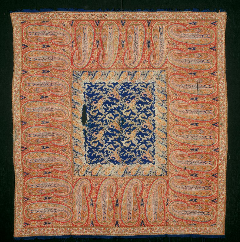 Shawl, printed in colors on fine cream-colored wool. Central panel of interlocking pear-motifs and trailing floral sprays on dark blue ground edged with border of pear-motifs filled with floral vines and geometric designs on red ground. Narrow outer border of running flower and vine pattern. Narrow blue borders at ends with remains of twisted blue silk fringe. Shawl badly worn and torn in center and borders. Printed fabric.