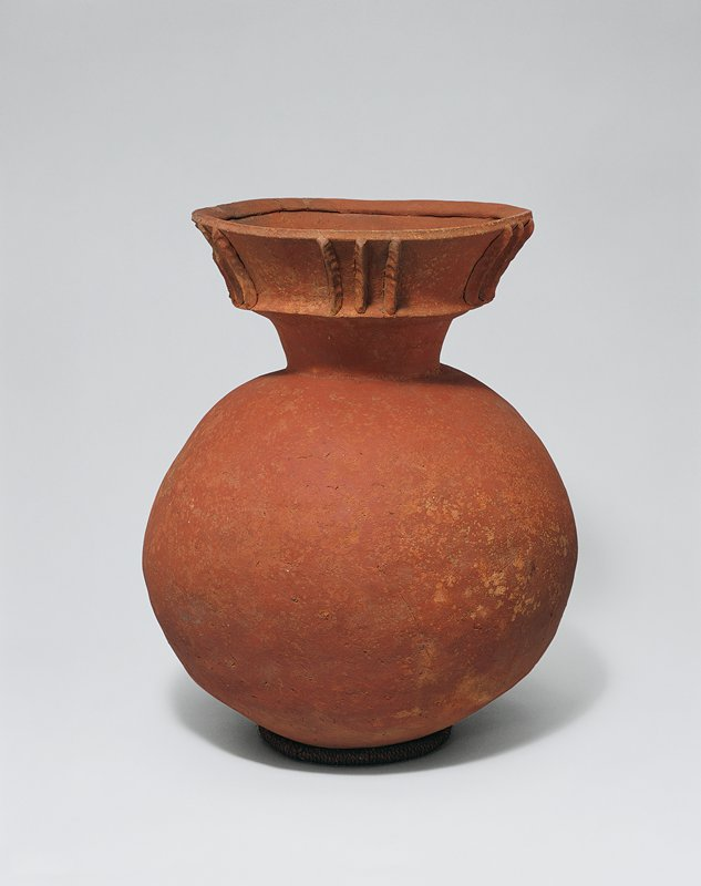 bright red clay jar with rounded body; flaring mouth decorated with three vertical clay strips; dark areas on body from firing