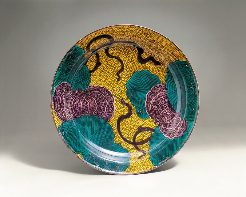large plate with two purple stylized pumpkins among brilliant, jewel toned green leaves; sinuous vines; yellow background with tiny circles; stylized swirling cloud motif on underside with emerald green background