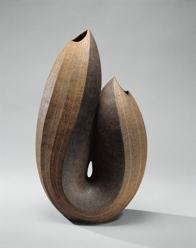 organic, faceted U-shaped vase, with small mouth near top of each element; ashy brown glaze, lighter at outer faces; thin beige lines within facets