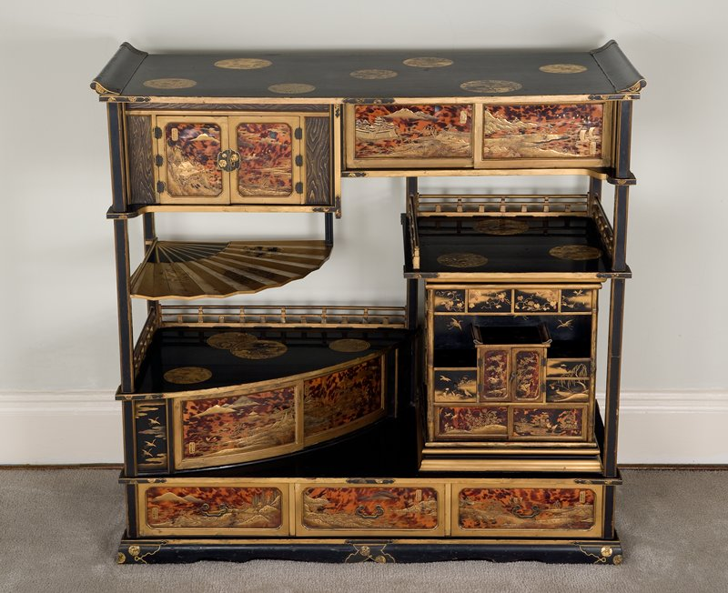 shelf stand with shelves of various dimensions (one at left is shaped like an open fan), doors set with tortoise shell and a revolving square cabinet with a variety of small doors; top decorated with gold roundels with flower and bird motifs; landscape scenes depict the 8 Views of Omi--landscapes with figures, boats, birds, insects, foliage