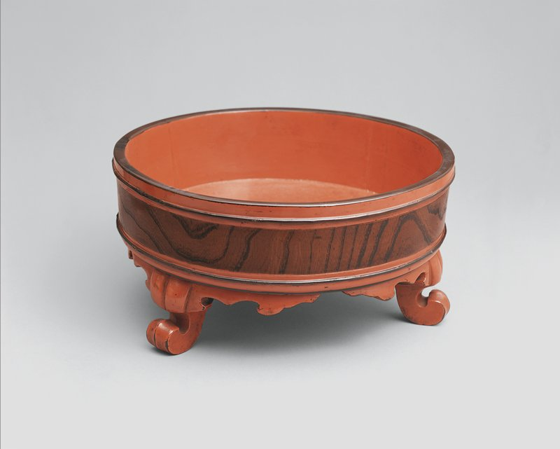 round basin with low walls, rests on three carved, scrolling feet; red lacquer with black detail; natural woodgrain body