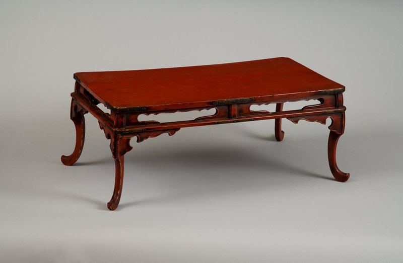 low red lacquer table with gracefully curving legs that come to a point; scalloped cutouts on sides between tabletop and support; decorated metal brackets at rounded edges