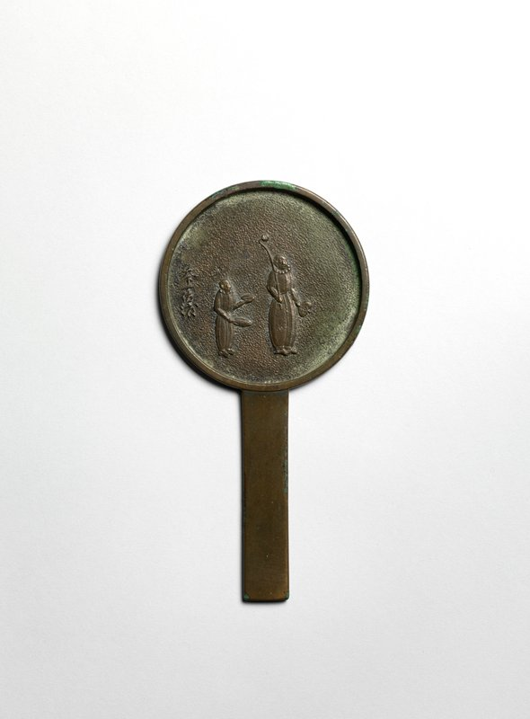 circular bronze mirror with two possibly Portuguese figures in low relief; one figure is taller, carrying two circular objects in PL hand, and object on pole over PR shoulder; second figure is shorter, carrying a plate and tray in each hand; comes with wooden display plaque