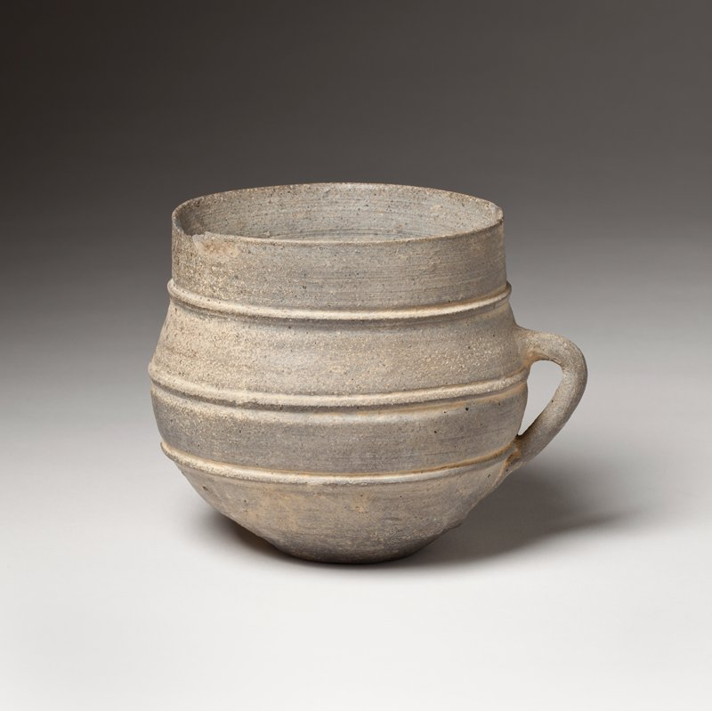 thin cup with three raised bands, very narrow foot, angled, looped handle