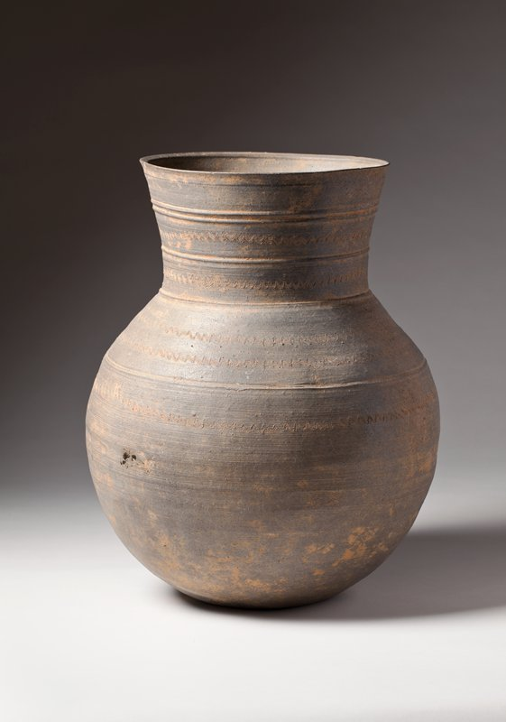 bulbous, round bottomed jar with flaring neck and wide mouth; five bands of wavy incised lines, and five incised ribbed bands