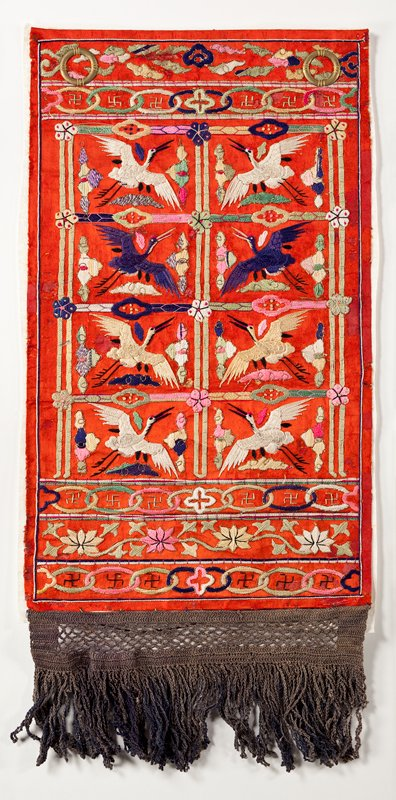 red silk panel with dark gray fringe at bottom; brightly embroidered with images of flying cranes facing each other in grid like pattern; floral and ring patterns in borders