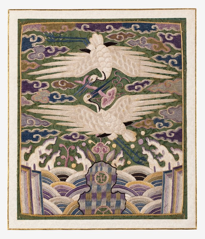 square panel of embroidered green silk; two white cranes at center with wings outward, facing each other, one above the other; pink, blue, purple, and tan clouds; abstracted wave motif at bottom with checkered pattern at bottom center