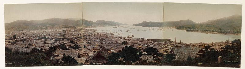 panoramic view of densely packed rooftops and trees along a bay surrounded by mountains, and filled with boats