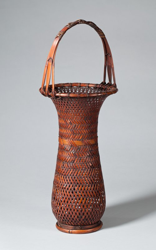 tall, round basket that tapers near top of body before flaring outward at mouth; chevron wave design with lighter band of three strips around center; handle made of three strips of bamboo with five decorative knots joining thm together at top; slight foot