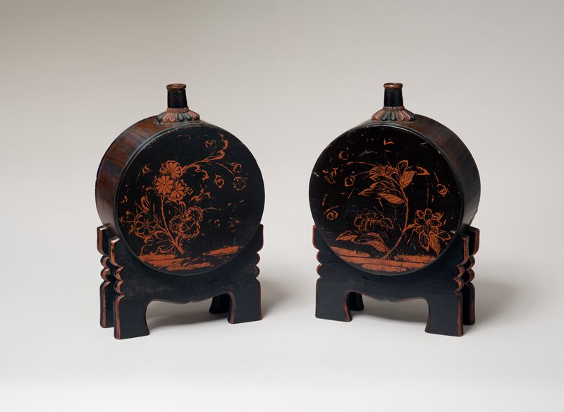one of two sake containers in the shape of a large drum with attached supports shaped like drum-stands; painted chrysanthemums on one side; another flowering plant on opposite side, with blossom on curving thin stem, and two smaller flowers on R and L; base of spout shaped like chrysanthemum