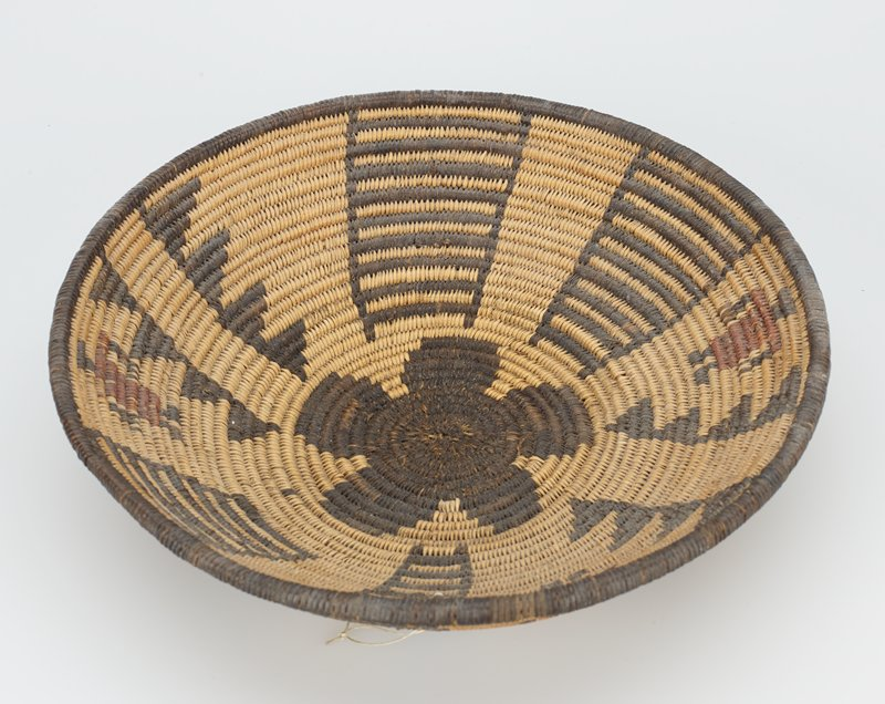 black and tan woven dish with black flower in center; four ladder designs and 3 figures with red tunics