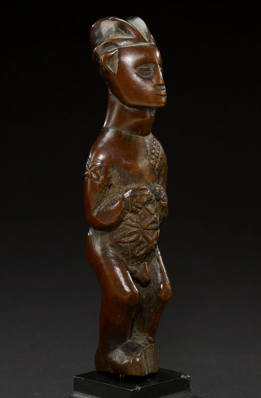 standing male figure carved from wood; knees are slightly bent and he holds an object against his midriff; thick strands of hair pull away from his forehead, giving the impression of a headdress; shallow carvings indicate oval eyes and a thin mouth; nose is square and protrudes slightly; two ears rest high up on either side of the figure's head; his chest is bare, besides a grid-like pattern carved into the right side of his chest--this pattern is also present on PL shoulder blade; carvings in his pubic region lead down to his exposed genitalia; figure's feet are square and create the base; flower carving on upper PR arms; the piece is a dark brown with slight sheen