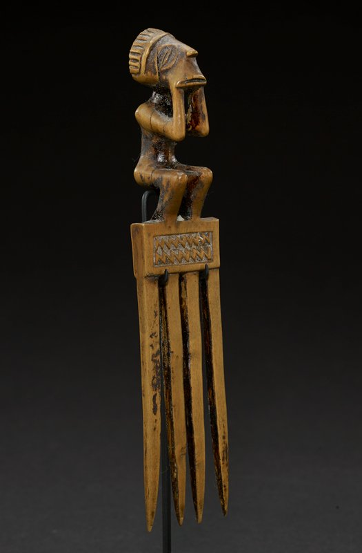comb with figure; comb is long and rectangular, with four wide teeth and a rectangular base, carved with patterns; on top of base is a seated figure whose feet rest on the top of the base; figure's legs bend at knees and torso is square; arms are bent at elbows, so that hands rest on either sides of the face; face has wide, thin mouth, a small nose that points straight ahead, and two large, oval eyes that rest flat on either side of head; on top of head is a striped band, that has a flat top and protrudes out into space; tan in color overall