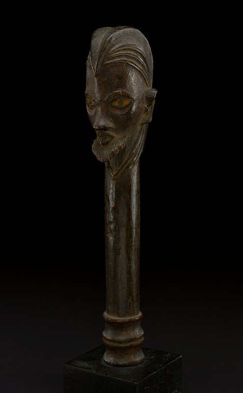 staff scepter; top of the scepter is carved as a male human head; top of the head is wearing a pointed headdress or helmet; figure's hair is carved around the helmet and ends down below the chin; ears are carved at the side of the head; figure has thick eyebrows and wide yellow mirror eyes with black pupils sealed in resin; traces of tukula under the eyes; nose is carved and prominent; lip are small and pursed; chin is covered in a short beard; the rest of the figure is the body of the staff; base of the staff has carved detailing at the bottom and tapers slightly; wood is dark brown except for eyes
