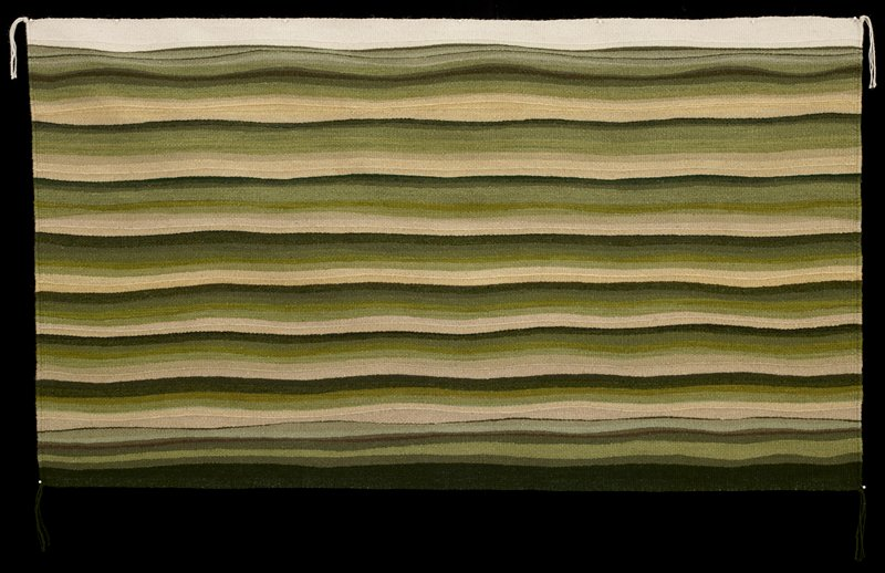 horizontal, slightly wavy stripes; light cream at top with shades of green, brown and grey; cream tassels at top corners, dark green tassels at bottom corners; some raised twisted ribs
