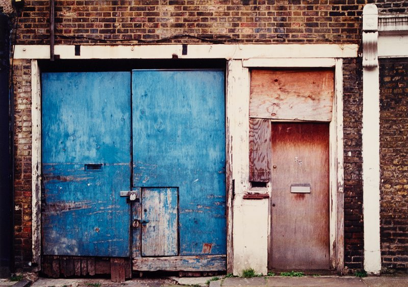 pair of worn blue wooden doors closed with two padlocks at left; one wooden door, with two plywood panels patching holes above and to left of door, at right side of image; brick wall
