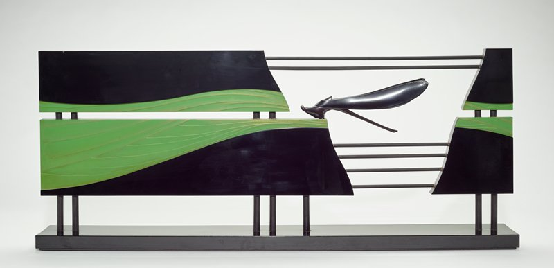 a decorative stand comprised of two horizontal panels in four pieces, frame a three dimensional dragonfly figure; several round, black metal bars run above and below the dragonfly, and run vertically to connect the panels with a rectangular base below; the stand's components are primarily black lacquer; however, the panels each have green areas, with hints of gold and silver, that suggest blowing grasses and/or flowing water with swooping and varied lines, and the dragonfly has iridescent purple and blue chips in its wings and around its eyes and a spray of silver color on its back and lower wings