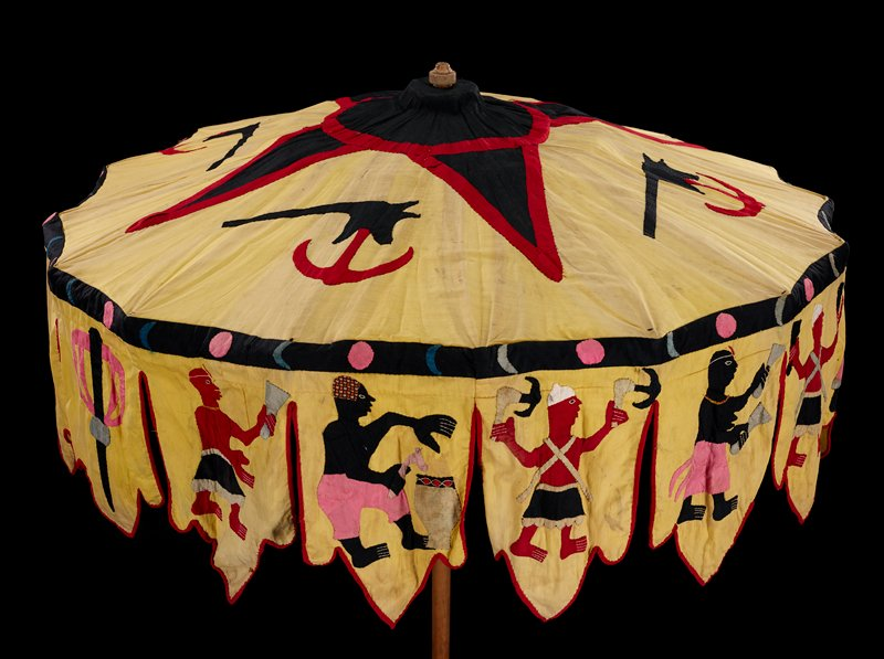 parasol on long wooden staff; wooden and metal mechanism; cloth parasol attached to wooden elements with strips of yellow cloth; white on underside; hanging pendants around edges of parasol, with appliques of figures with tools, pots, snakes, staff, tree and hut with pink and black object; top is yellow with red and black trim, with red and black applique symbols or tools (?); edge has black trim with pink circles and blue and grey crescents