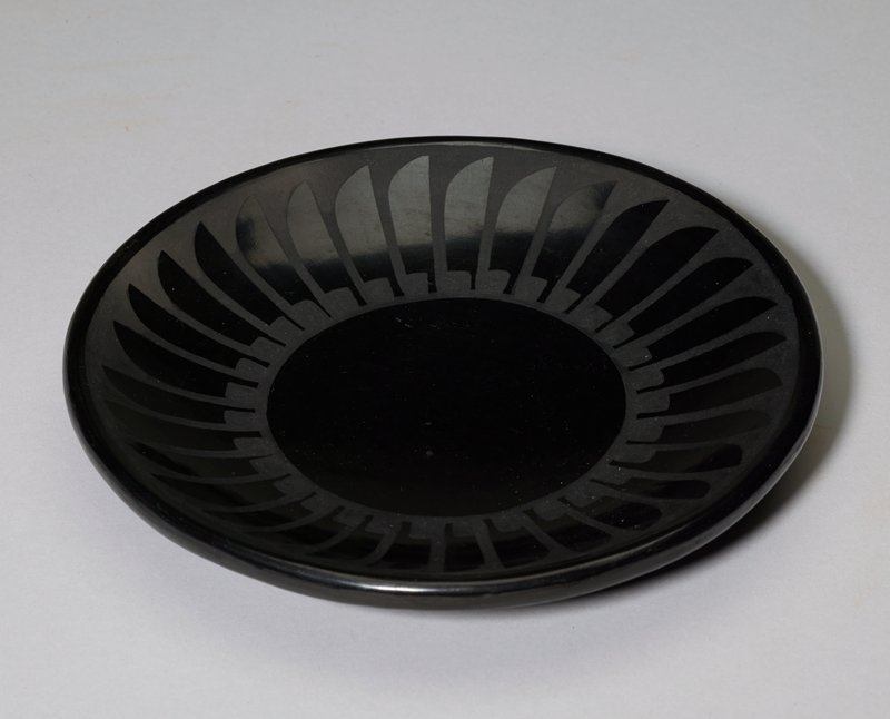 small saucer with flat bottom; shiny black and matte dark grey; rim decorated with repeating feather shapes