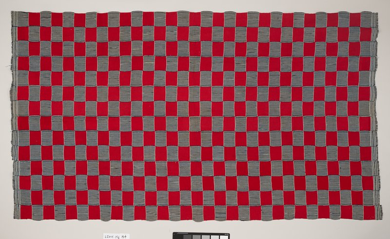 stitched panel with checkered pattern; red fabric alternates with blue and white patterned fabric; two ends of panel and lined with fringe with same blue and white fabric