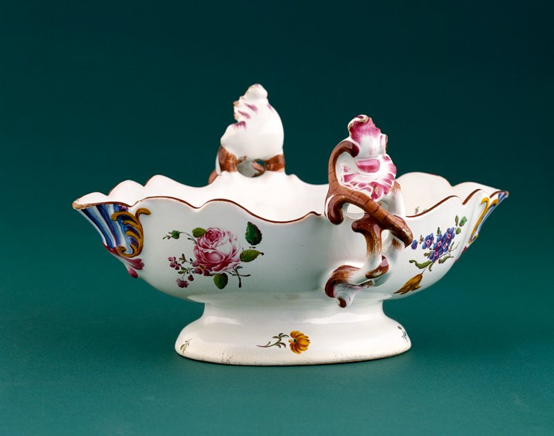 oval faience bowl with scalloped edge; rim decorated in brown; twisted branches entwining rocaille scroll-form handles; both interior and exterior are decorated with roses, tulips, cowslips and other small flowers; lip at either end decorated with rococo scrollwork and stripes