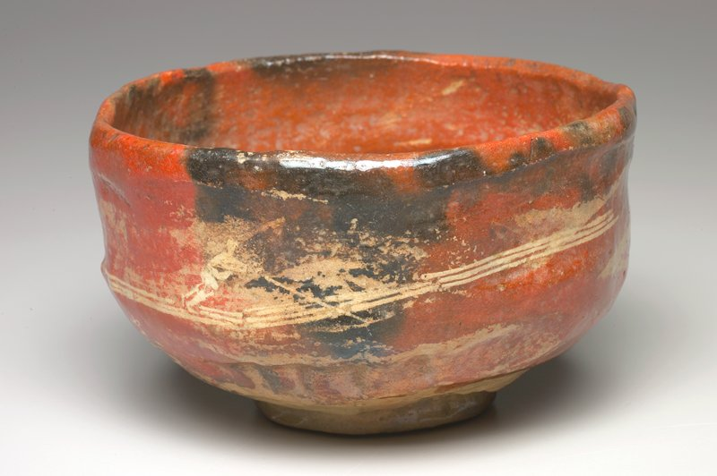 Tea Bowl roughly made; red glaze; man on a raft and seal in yellow paint on sides