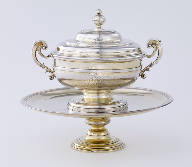 bowl has two scroll handles and stands on a low moulded foot; a plain compressed knob surmounts the domed moulded cover, engraved on the cover and body with the Crown and the initials of the Earl of Ancaster and Kestinen; salver-on-foot is plain and circular with moulded edge; tall circular foot with moulded base; center engraved with Crown and the initials of the Earl of Ancaste and Kestinen