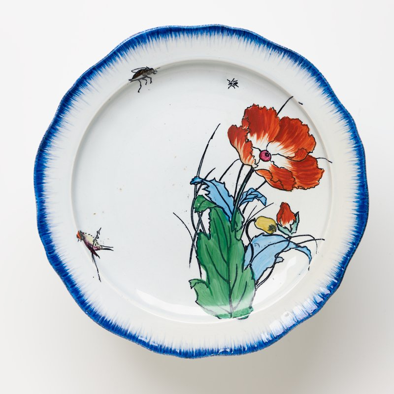 cake plate with white ground and brushed blue pigment around edge of plate and foot with painted flower, small bird, beetle and ant on plate surface and a yellow flower, lavender butterfly and an ant on foot