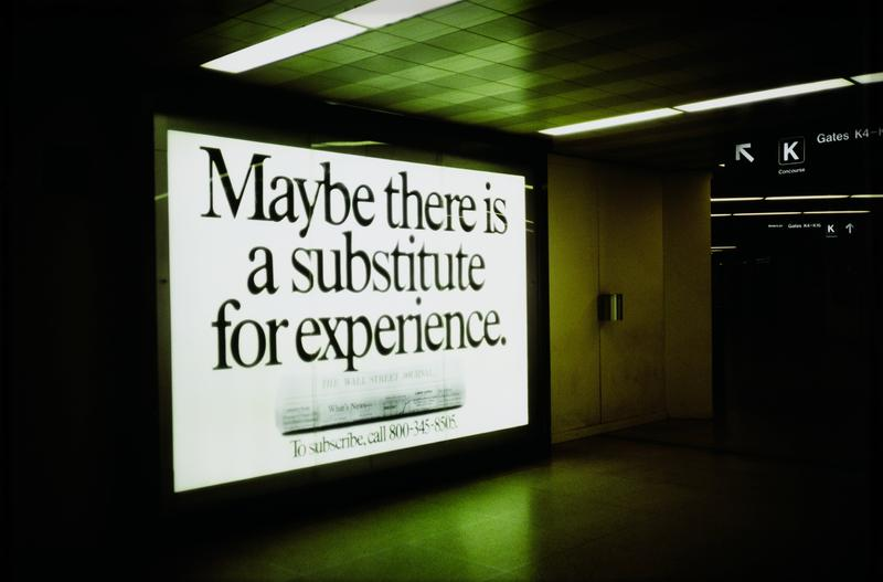 "hallway scene with large advertisement for Wall Street Journal, reading ""Maybe there is a Substitute for Experience"" at L; sign pointing the way to terminal K around corner at UR"