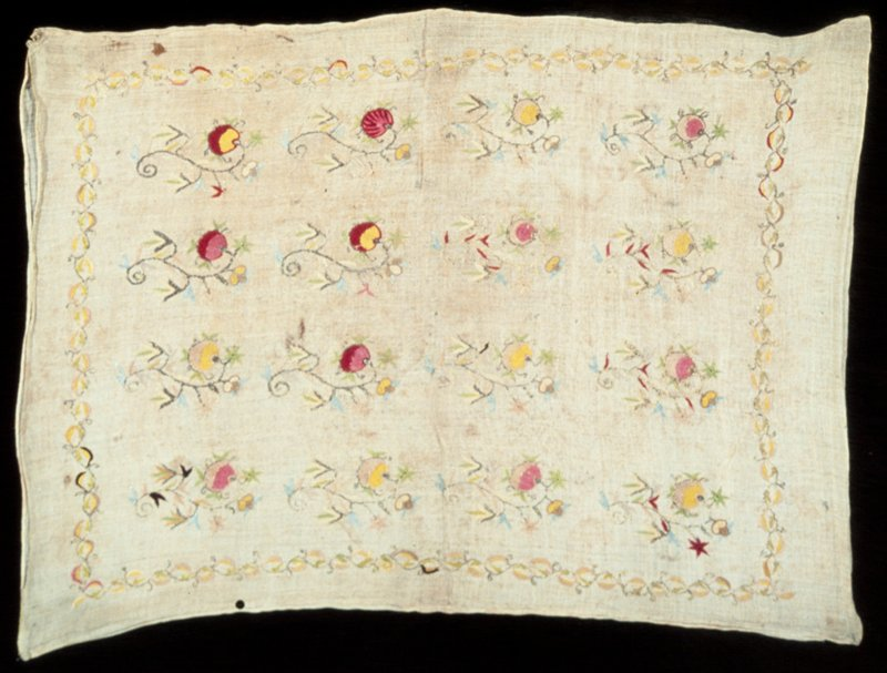 loosely woven linen embroidered with colored silks in rows of floral sprays