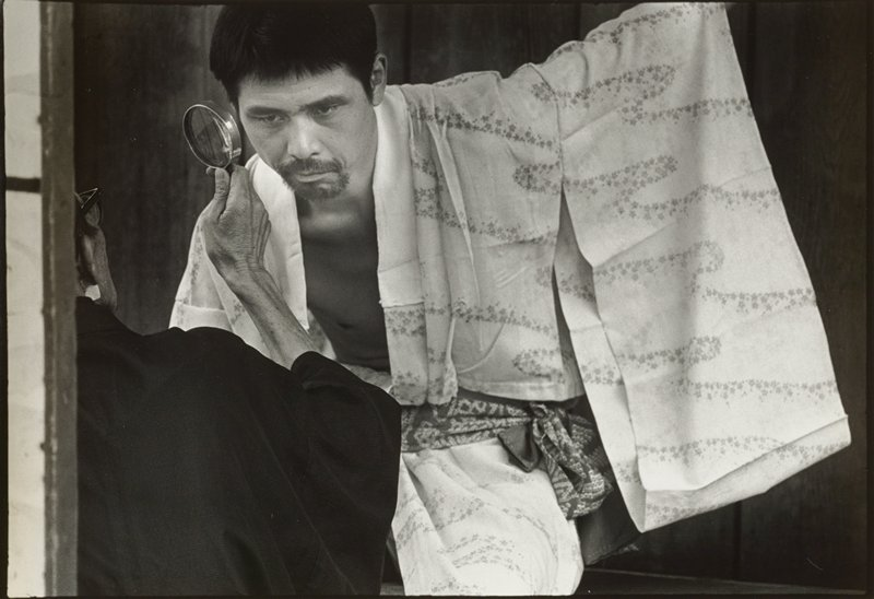man with short black hair and goatee wearing a kimono with flowers in wave-like patterns, bending slightly downward; figure wearing glasses and a dark robe at left, seen from back, looking at man's PL ear with a magnifying glass