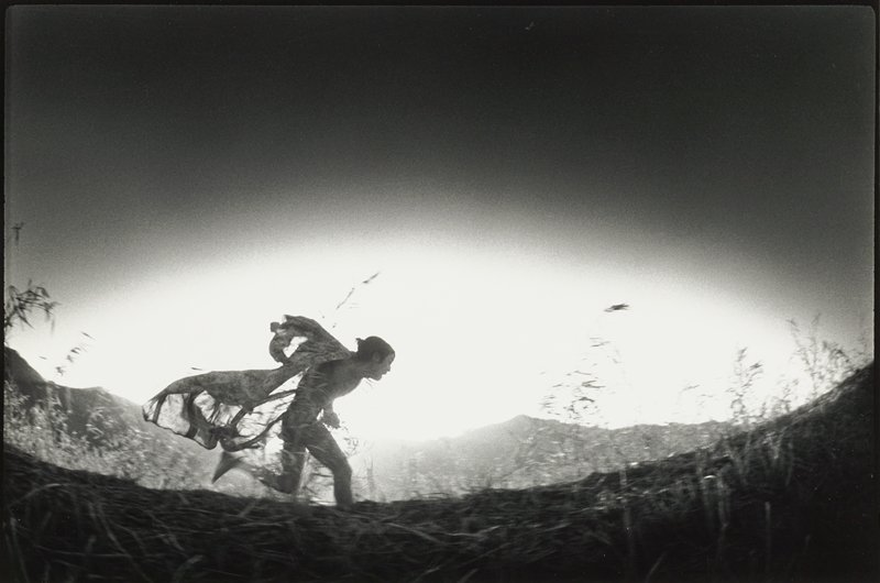 running man wearing open thin kimono flowing behind him; low horizon line; some silhouettes of grasses in foreground