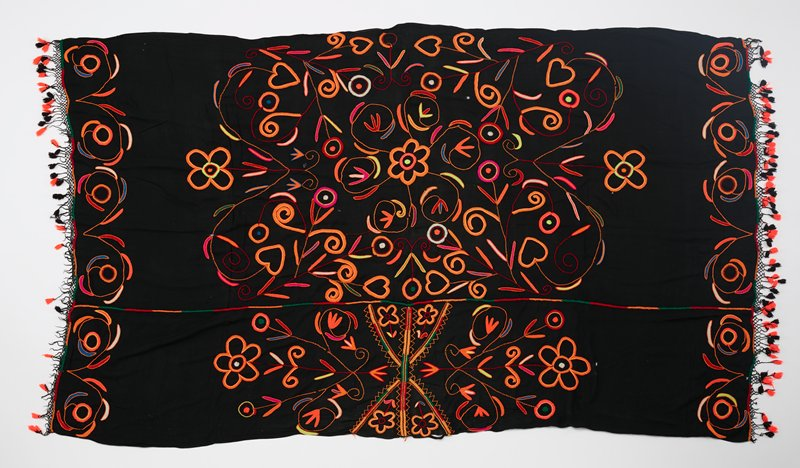 black ground fabric; embroidered in predominately orange with floral motifs; looping symmetrical organic motif border bands at short sides; red, orange and green band off-center; short ends have netting trim with orange and black tassels
