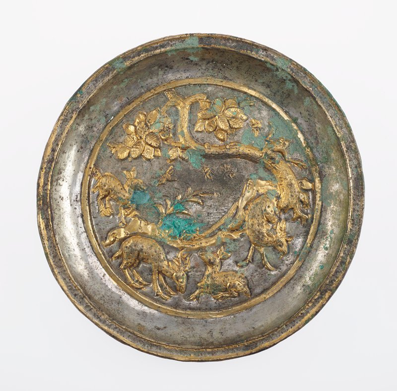 small silver dish with raised gold colored decoration of grazing deer, mountains, and bent tree with a monkey; gold band separating scene from wall; lip is decorated with zigzag and spot incised lines