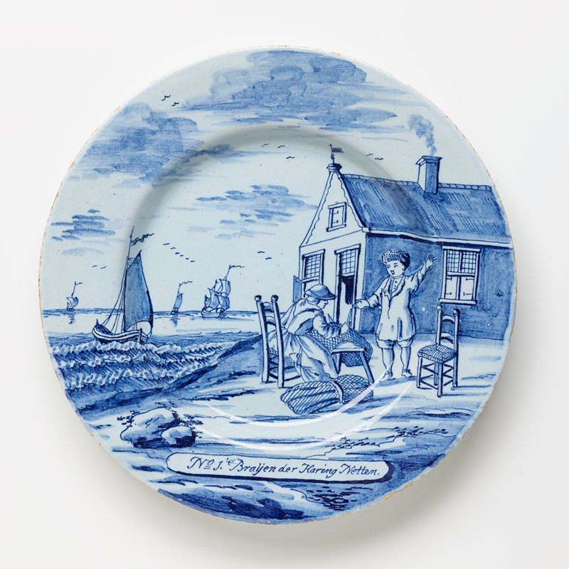 woman sitting on chair, making fishing net; boy standing opposite, gesturing and smiling; house at R; shore with ships at L