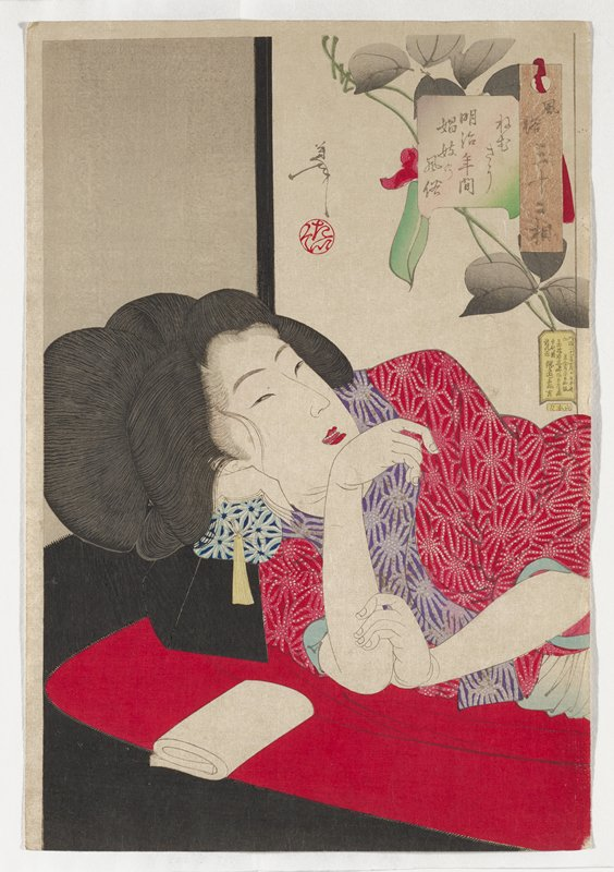 woman lying on a red pallet with a black neckrest and blue and white pillow with yellow tassel beneath her head; woman wears a red and white abstract floral patterned kimono with similar purple pattern around neckline; floral screen behind woman